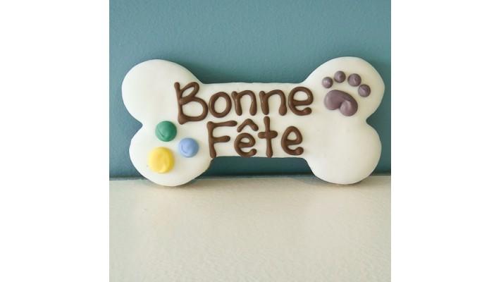 Biscuit sec pour chien au beurre d'arachide en forme d'os avec écriture Bonne fête en glaçage
